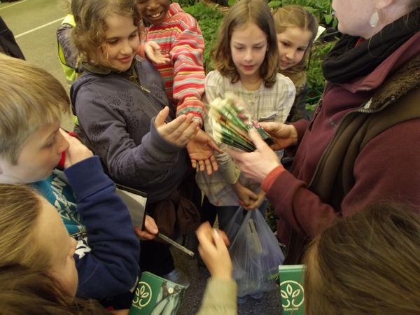 Recreamomes @ Lugny - Emilie remet des sachets de graines aux enfants venus visiter la Coopérative Agricole
